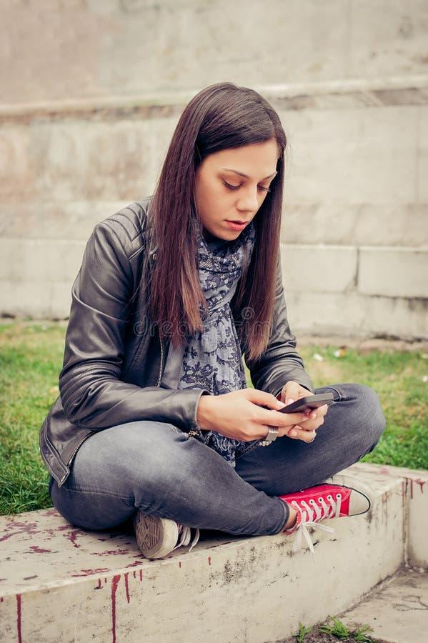 Συνεδρίαση γυναικών στην οδό πόλεων, μήνυμα δακτυλογράφησης, που κουβεντιάζει στο smartp στοκ φωτογραφία με δικαίωμα ελεύθερης χρήσης