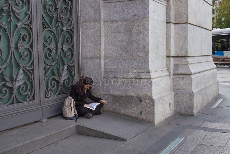 Συνεδρίαση γυναικών στην πόρτα της τράπεζας της Ισπανίας στοκ εικόνα με δικαίωμα ελεύθερης χρήσης