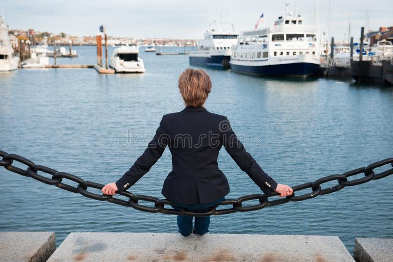 Συνεδρίαση γυναικών στην ωκεάνια αποβάθρα που σκέφτεται και που ονειρεύεται πίσω όψη στοκ φωτογραφία με δικαίωμα ελεύθερης χρήσης