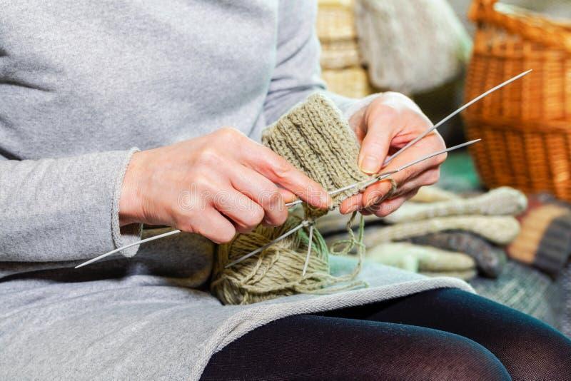 Συνεδρίαση γυναικών στον καναπέ και πλέξιμο στοκ εικόνα