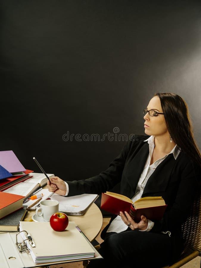 Συνεδρίαση γυναικών στο γράψιμο γραφείων της στοκ φωτογραφία