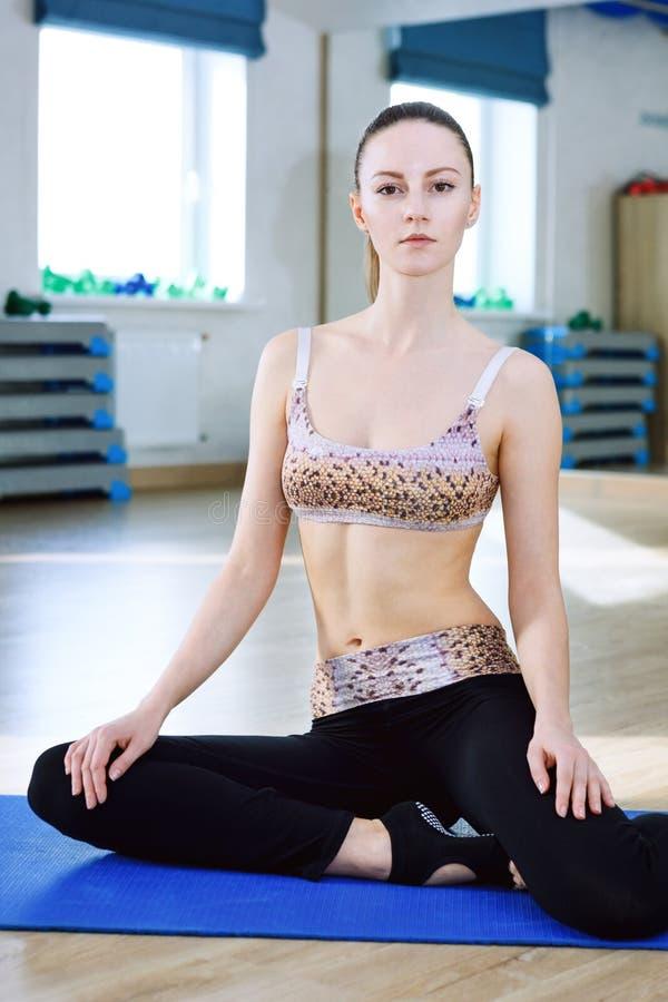 Συνεδρίαση γυναικών στο ρόδινο ypga ματ και που κάνει τις ασκήσεις στη γυμναστική λεσχών ικανότητας στοκ εικόνα με δικαίωμα ελεύθερης χρήσης