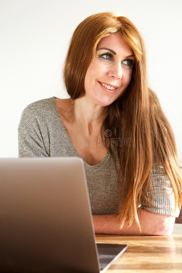 Συνεδρίαση γυναικών χαμόγελου ώριμη στον πίνακα με το lap-top στοκ φωτογραφίες