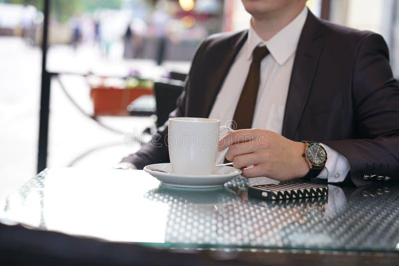 Συνεδρίαση επιχειρηματιών με ένα φλιτζάνι του καφέ και ένα τηλέφωνο σε έναν μαύρο πίνακα με μια αντανάκλαση στοκ εικόνες