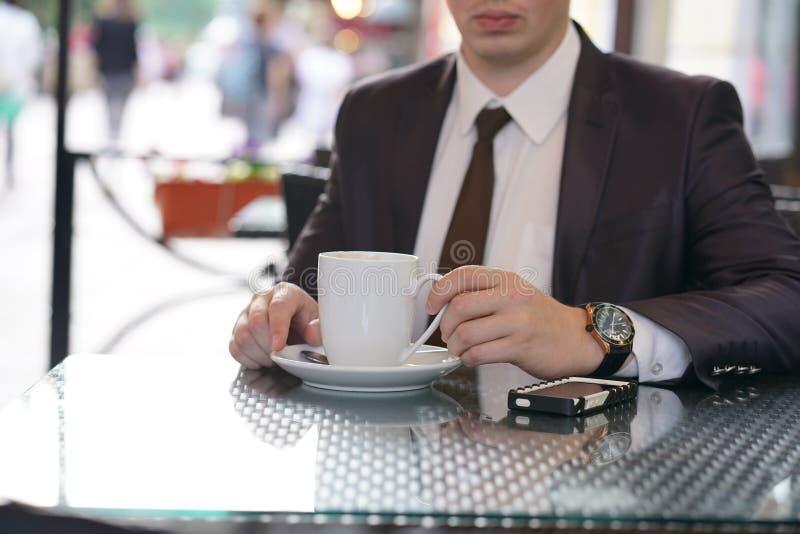 Συνεδρίαση επιχειρηματιών με ένα φλιτζάνι του καφέ και ένα τηλέφωνο σε έναν μαύρο πίνακα με μια αντανάκλαση στοκ φωτογραφία