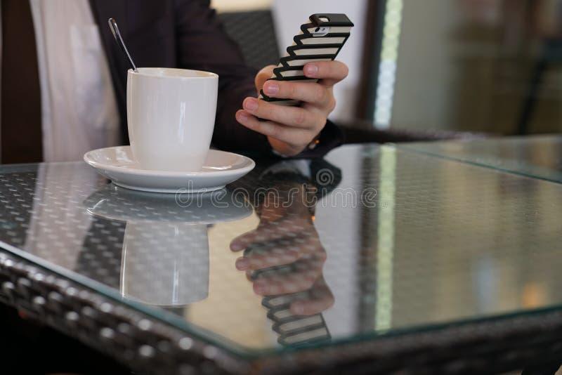 Συνεδρίαση επιχειρηματιών με ένα φλιτζάνι του καφέ και ένα τηλέφωνο σε έναν μαύρο πίνακα με μια αντανάκλαση στοκ φωτογραφίες με δικαίωμα ελεύθερης χρήσης