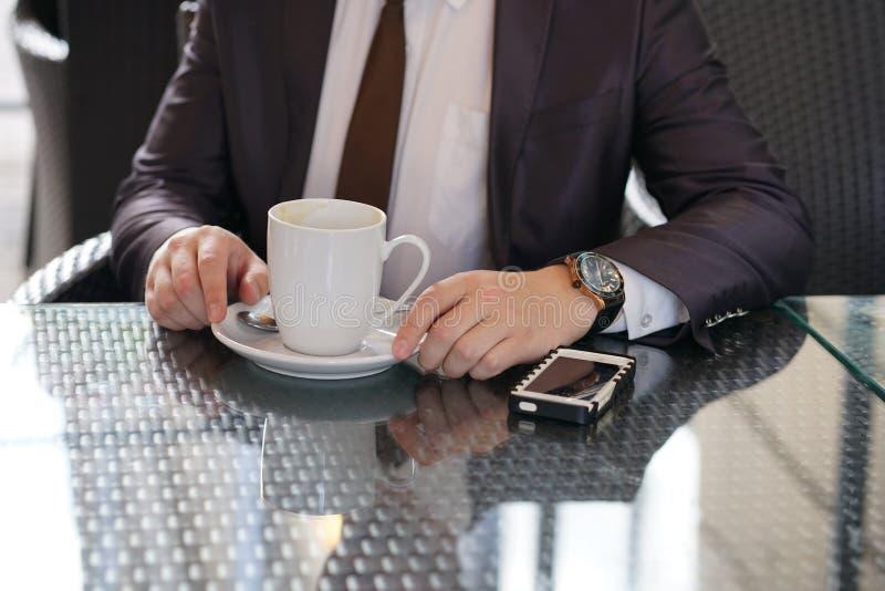 Συνεδρίαση επιχειρηματιών με ένα φλιτζάνι του καφέ και ένα τηλέφωνο σε έναν μαύρο πίνακα με μια αντανάκλαση στοκ φωτογραφίες