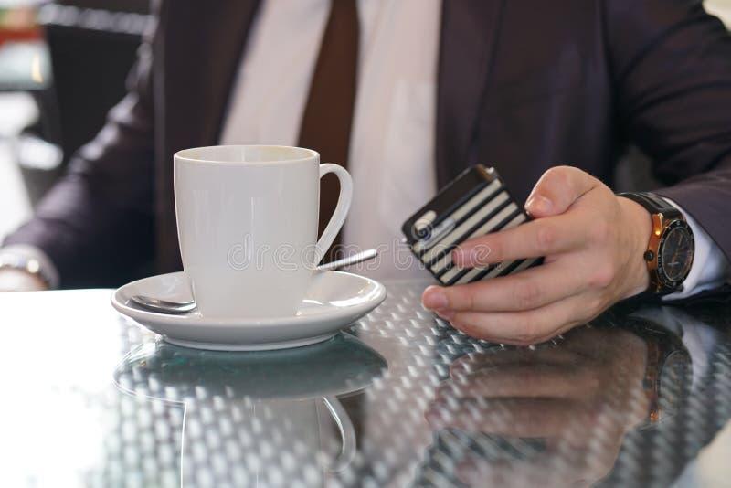Συνεδρίαση επιχειρηματιών με ένα φλιτζάνι του καφέ και ένα τηλέφωνο σε έναν μαύρο πίνακα με μια αντανάκλαση στοκ εικόνα