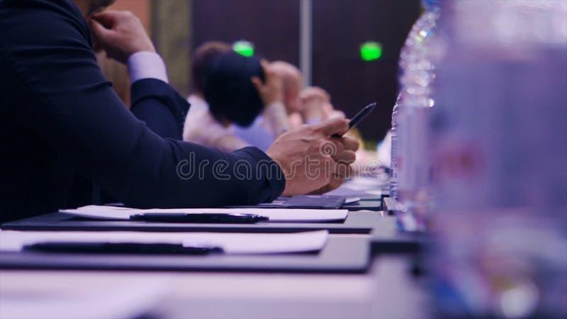 Συνεδρίαση επιχειρηματιών σε έναν πίνακα και εκμετάλλευση μια μάνδρα απόθεμα Επιχειρηματίας με μια μάνδρα στη διάσκεψη στοκ φωτογραφία με δικαίωμα ελεύθερης χρήσης