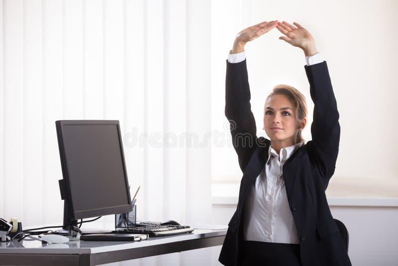 Συνεδρίαση επιχειρηματιών στην έδρα που τεντώνει τα όπλα της στοκ φωτογραφία με δικαίωμα ελεύθερης χρήσης