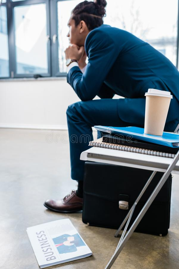 Συνεδρίαση επιχειρηματιών στην καρέκλα και αναμονή από το σωρό των εγγράφων στοκ φωτογραφία με δικαίωμα ελεύθερης χρήσης