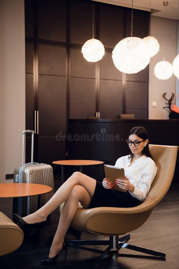 Συνεδρίαση επιχειρηματιών στο επιχειρησιακό σαλόνι αερολιμένων, αναμονή για την πτήση Χαμογελώντας γυναίκα που φορά τα γυαλιά που στοκ φωτογραφία με δικαίωμα ελεύθερης χρήσης