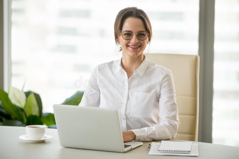 Συνεδρίαση επιχειρηματιών χαμόγελου χιλιετής στο γραφείο εργασίας με το lapto στοκ φωτογραφία