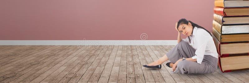 Συνεδρίαση επιχειρησιακών γυναικών στο πάτωμα δίπλα σε έναν σωρό των βιβλίων στοκ φωτογραφίες