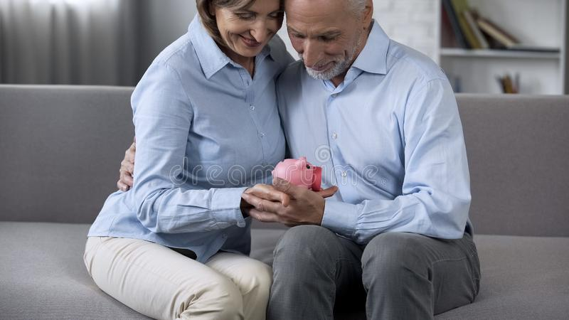 Συνεδρίαση ζευγών συνταξιούχων χαμόγελου στον καναπέ που κρατά τη piggy τράπεζα, που πιστώνει την υπηρεσία στοκ φωτογραφία
