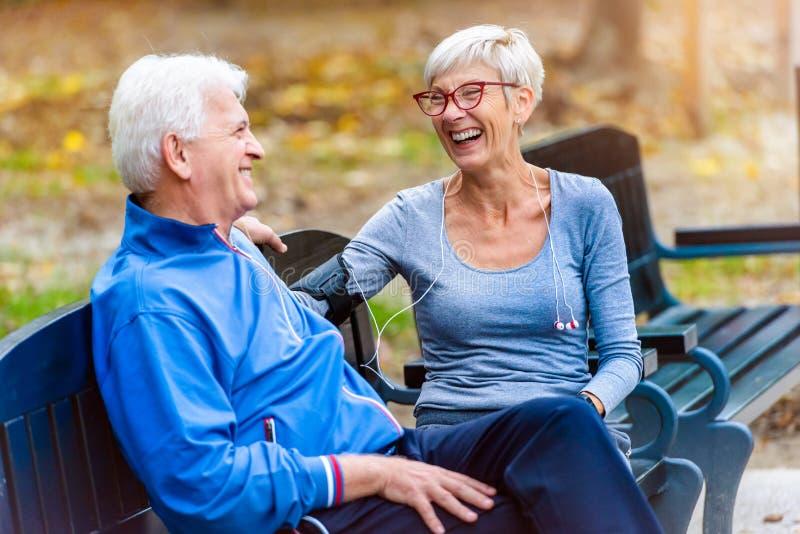 Συνεδρίαση ζευγών χαμόγελου ανώτερη στην ομιλία πάρκων στοκ φωτογραφία με δικαίωμα ελεύθερης χρήσης