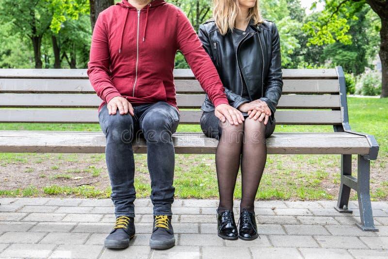 Συνεδρίαση ζεύγους σε έναν πάγκο, χέρι εκμετάλλευσης ανδρών στο γόνατο της γυναίκας στοκ εικόνες με δικαίωμα ελεύθερης χρήσης