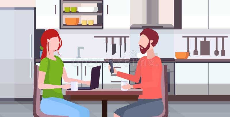 Συνεδρίαση ζεύγους στην επιτραπέζια γυναίκα που χρησιμοποιεί lap-top ανδρών εκμετάλλευσης σύγχρονη κουζίνα έννοιας εθισμού συσκευ απεικόνιση αποθεμάτων