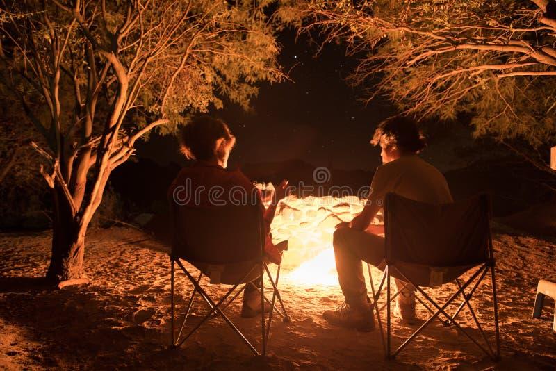 Συνεδρίαση ζεύγους στο κάψιμο της πυρκαγιάς στρατόπεδων στη νύχτα Στρατοπεδεύοντας στο δάσος κάτω από τον έναστρο ουρανό, Ναμίμπι στοκ εικόνες με δικαίωμα ελεύθερης χρήσης