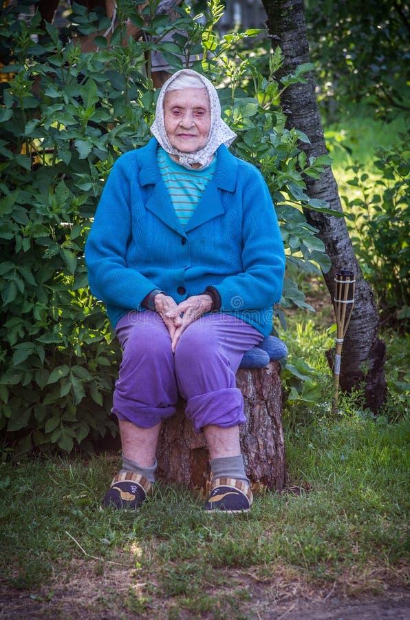 Συνεδρίαση ηλικιωμένων γυναικών σε ένα κούτσουρο, πολύ γηραιή καυκάσια κυρία στοκ φωτογραφίες με δικαίωμα ελεύθερης χρήσης