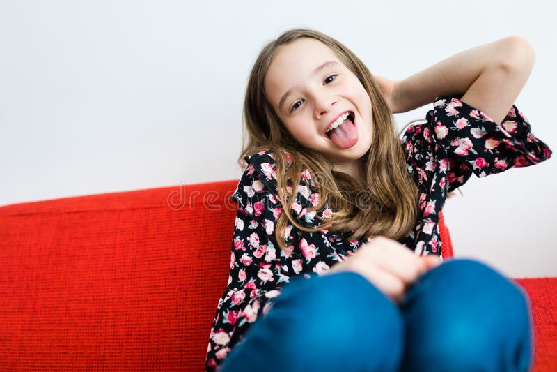 Συνεδρίαση κοριτσιών εφήβων χρονών και χαμόγελο στον κόκκινο καναπέ στοκ φωτογραφίες