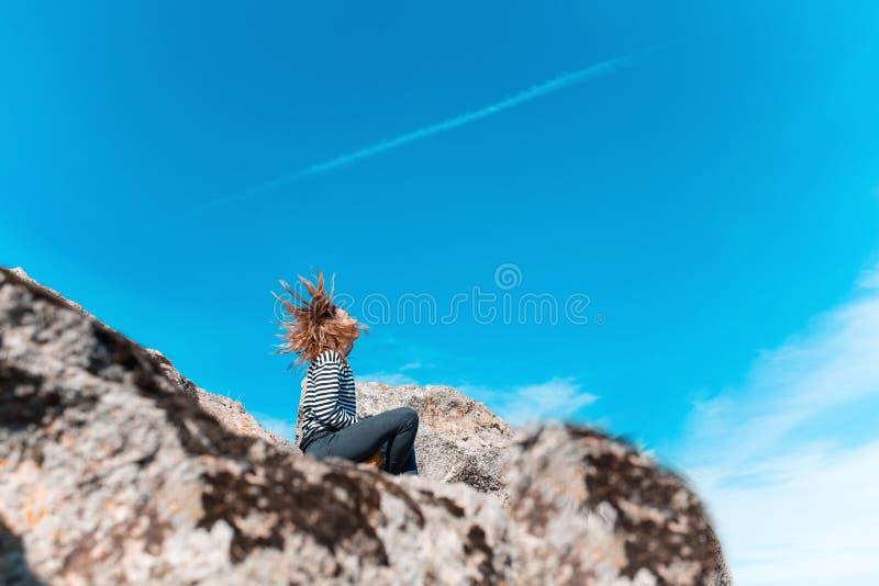 Συνεδρίαση κοριτσιών σε έναν απότομο βράχο που αγνοεί τον ουρανό με το φύσηγμα τρίχας της στοκ εικόνες με δικαίωμα ελεύθερης χρήσης