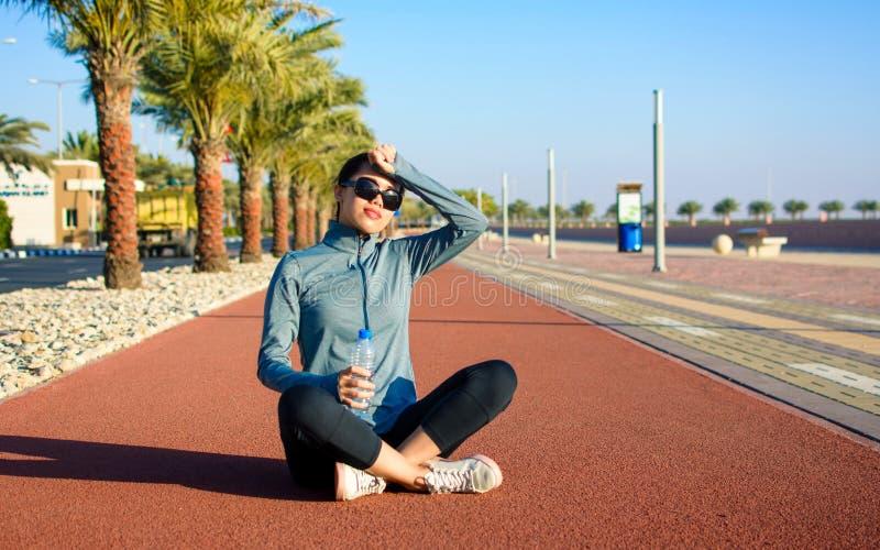 Συνεδρίαση κοριτσιών σε μια τρέχοντας διαδρομή και απόλαυση της ηλιόλουστης ημέρας στοκ εικόνες με δικαίωμα ελεύθερης χρήσης