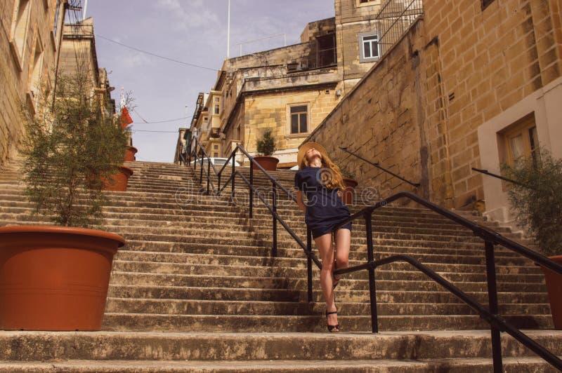 Συνεδρίαση κοριτσιών στα κιγκλιδώματα των σκαλοπατιών στην οδό, παλαιά πόλη των τριών πόλεων στοκ φωτογραφίες