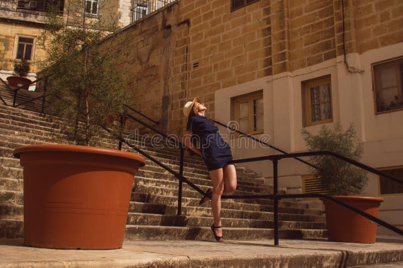Συνεδρίαση κοριτσιών στα κιγκλιδώματα των σκαλοπατιών στην οδό, παλαιά πόλη των τριών πόλεων στοκ εικόνα με δικαίωμα ελεύθερης χρήσης