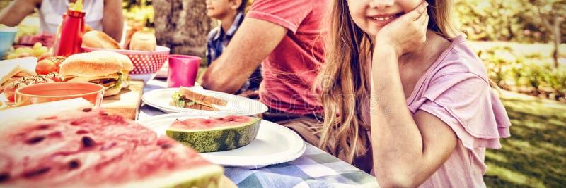 Συνεδρίαση κοριτσιών στον πίνακα με την κατοχή του γεύματος whith η οικογένειά της στο πάρκο στοκ εικόνες