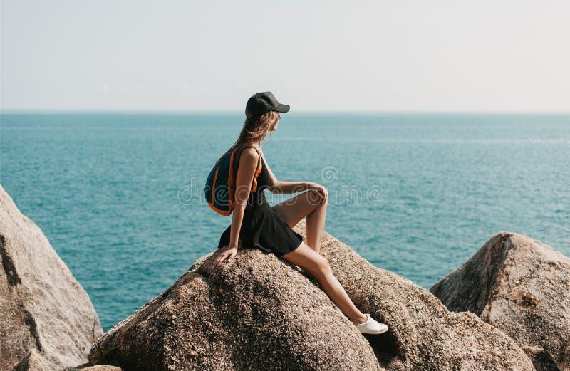 συνεδρίαση κοριτσιών στους βράχους και κοίταγμα στοκ φωτογραφίες