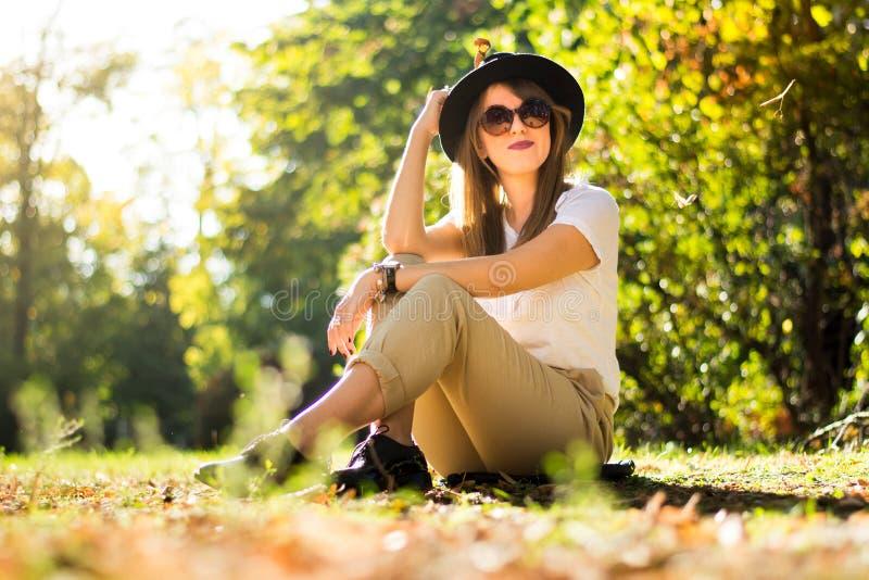 Συνεδρίαση κοριτσιών στο πάρκο που καλύπτεται με τα φύλλα φθινοπώρου στοκ εικόνες με δικαίωμα ελεύθερης χρήσης