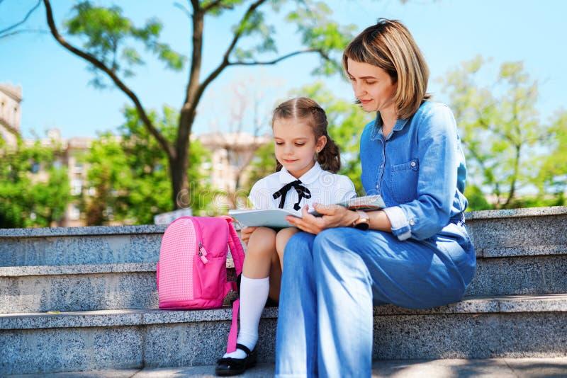 Συνεδρίαση κορών μητέρων και παιδάκι στα σκαλοπάτια και το διαβασμένο βιβλίο, μαθήματα μελέτης Πατρότητα και έννοια παιδιών στοκ φωτογραφίες με δικαίωμα ελεύθερης χρήσης
