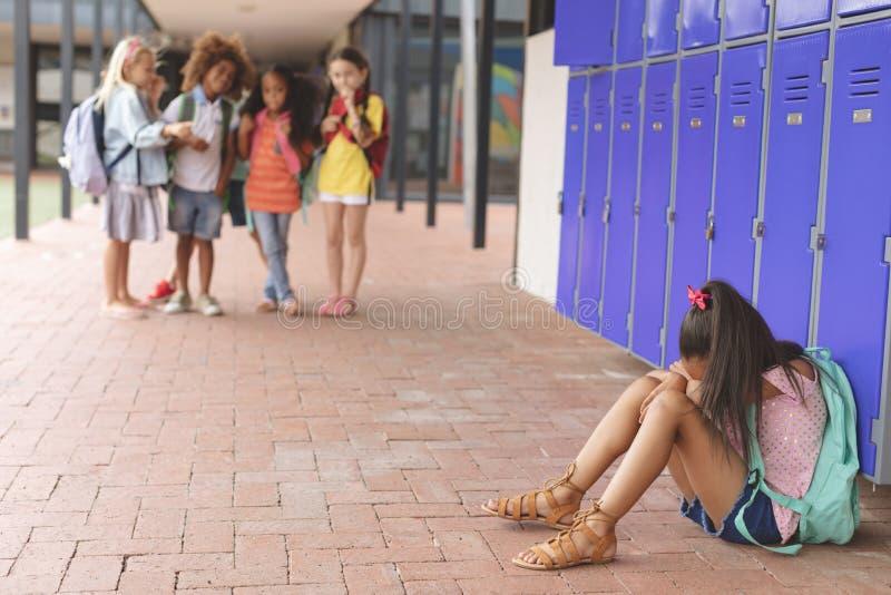 Συνεδρίαση μαθητριών μόνο στο σχολικό διάδρομο ενώ άλλοι σχολικά παιδιά που εξετάζουν την στοκ φωτογραφίες