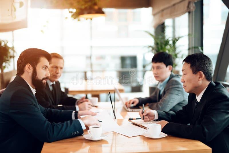 Συνεδρίαση με τους κινεζικούς επιχειρηματίες στο εστιατόριο Συζητούν το σημείο στα έγγραφα στοκ εικόνα