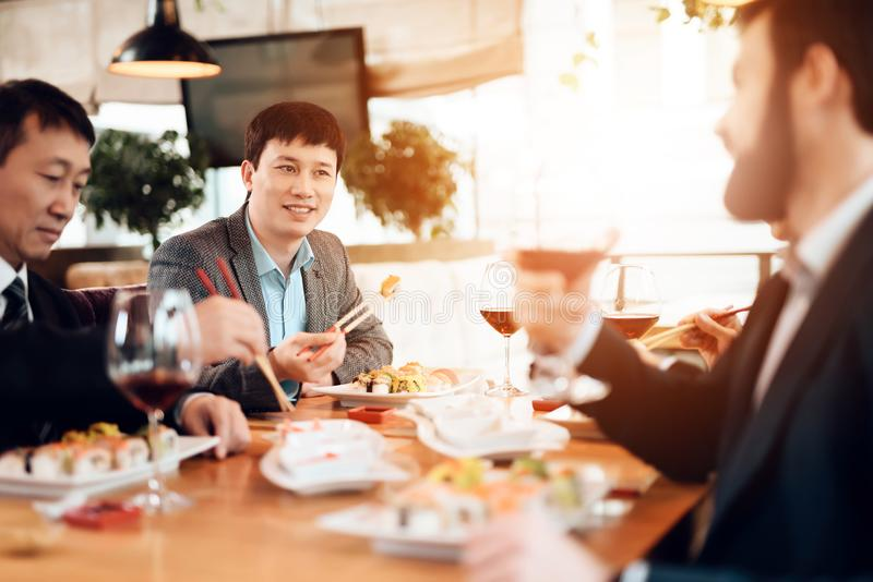 Συνεδρίαση με τους κινεζικούς επιχειρηματίες στο εστιατόριο Τα άτομα τρώνε τα σούσια στοκ φωτογραφίες με δικαίωμα ελεύθερης χρήσης