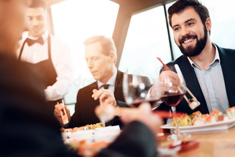 Συνεδρίαση με τους κινεζικούς επιχειρηματίες στο εστιατόριο Τα άτομα τρώνε τα σούσια στοκ φωτογραφία