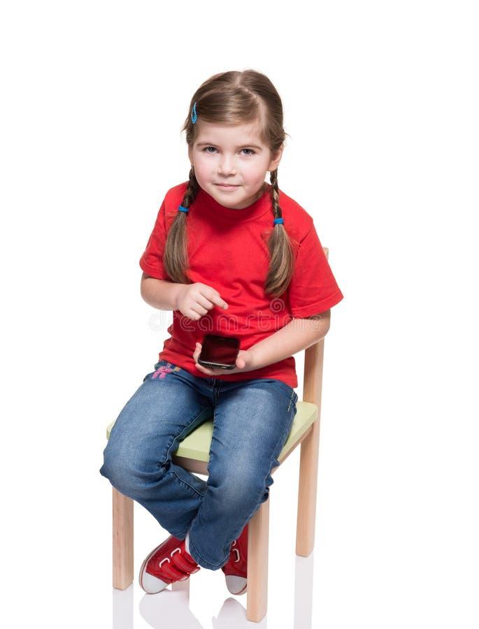 Συνεδρίαση μικρών κοριτσιών σε μια έδρα και χρησιμοποίηση του smartphone στοκ εικόνα με δικαίωμα ελεύθερης χρήσης