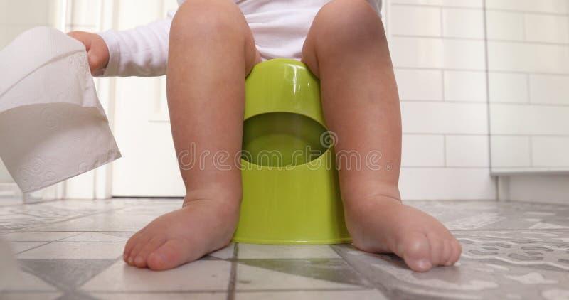 Συνεδρίαση μωρών chamberpot τα πόδια του που κρεμούν κάτω από το δοχείο στοκ εικόνες