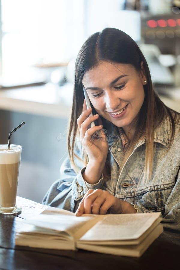 Συνεδρίαση νέων κοριτσιών σε έναν καφέ που διαβάζει ένα βιβλίο και που μιλά στο τηλέφωνο στοκ εικόνα με δικαίωμα ελεύθερης χρήσης