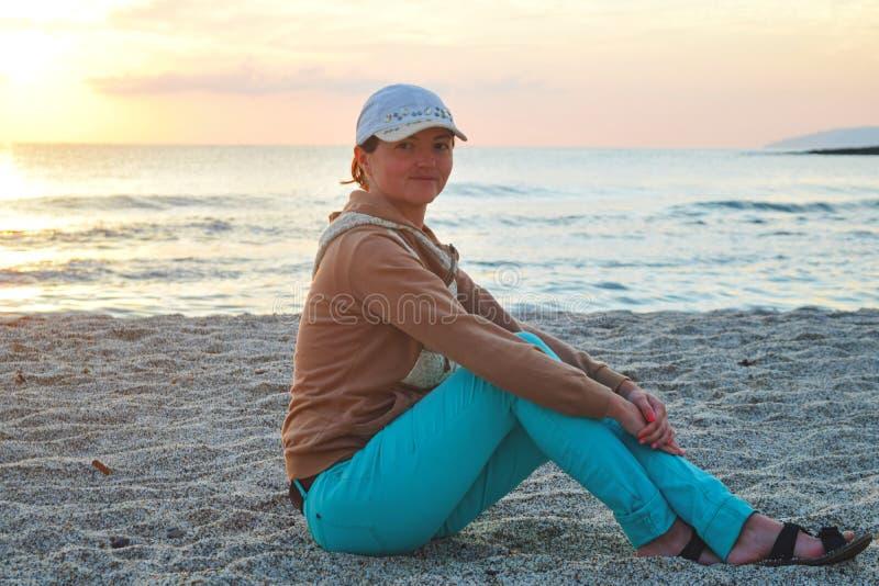 Συνεδρίαση νέων κοριτσιών στην άμμο θαλασσίως στην ανατολή στοκ εικόνες