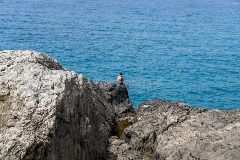 Συνεδρίαση νεαρών άνδρων σε έναν απότομο βράχο στοκ εικόνα