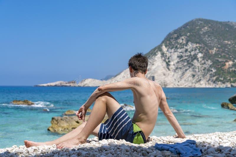 Συνεδρίαση νεαρών άνδρων σε μια παραλία πετρών στοκ φωτογραφία