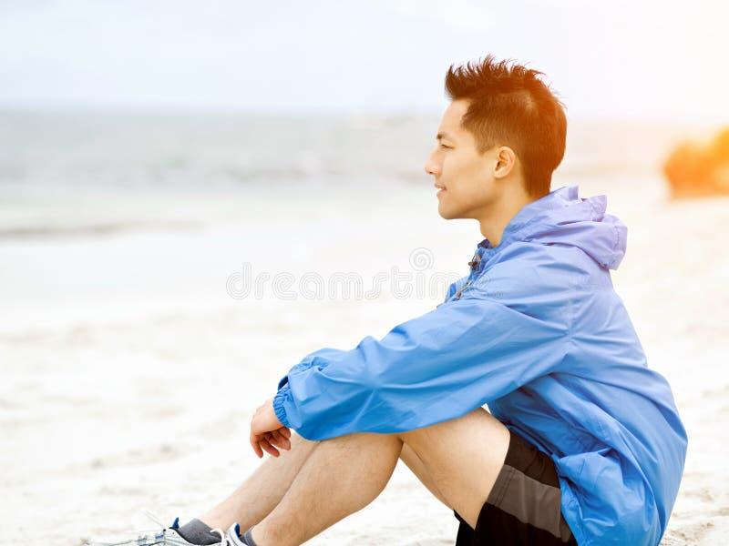 Συνεδρίαση νεαρών άνδρων στην παραλία sportswear στοκ εικόνες