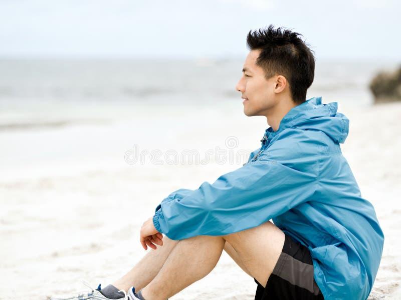 Συνεδρίαση νεαρών άνδρων στην παραλία sportswear στοκ φωτογραφία με δικαίωμα ελεύθερης χρήσης