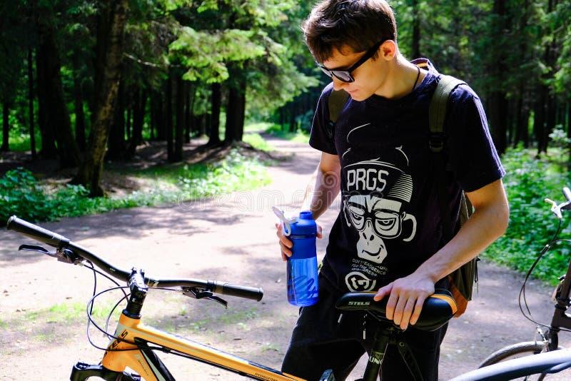 Συνεδρίαση νεαρών άνδρων στο βουνό κοντά στο ποδήλατο Κοιτάζει ονειρεμένα στην απόσταση Αθλητικός τρόπος ζωής r r στοκ εικόνες με δικαίωμα ελεύθερης χρήσης