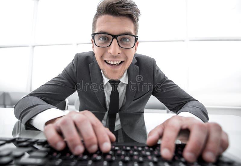 Συνεδρίαση νεαρών άνδρων στο γραφείο με τα χέρια στο πληκτρολόγιο και να φανεί clo στοκ φωτογραφία με δικαίωμα ελεύθερης χρήσης
