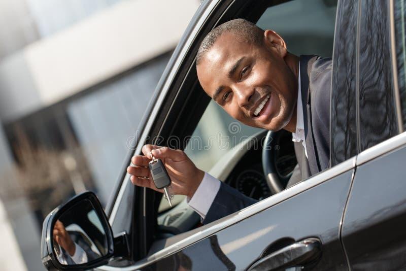 Συνεδρίαση νεαρών άνδρων στο νέο αυτοκίνητο που κοιτάζει έξω από το παράθυρο με το κλειδί που φαίνεται κάμερα εύθυμη στοκ εικόνες