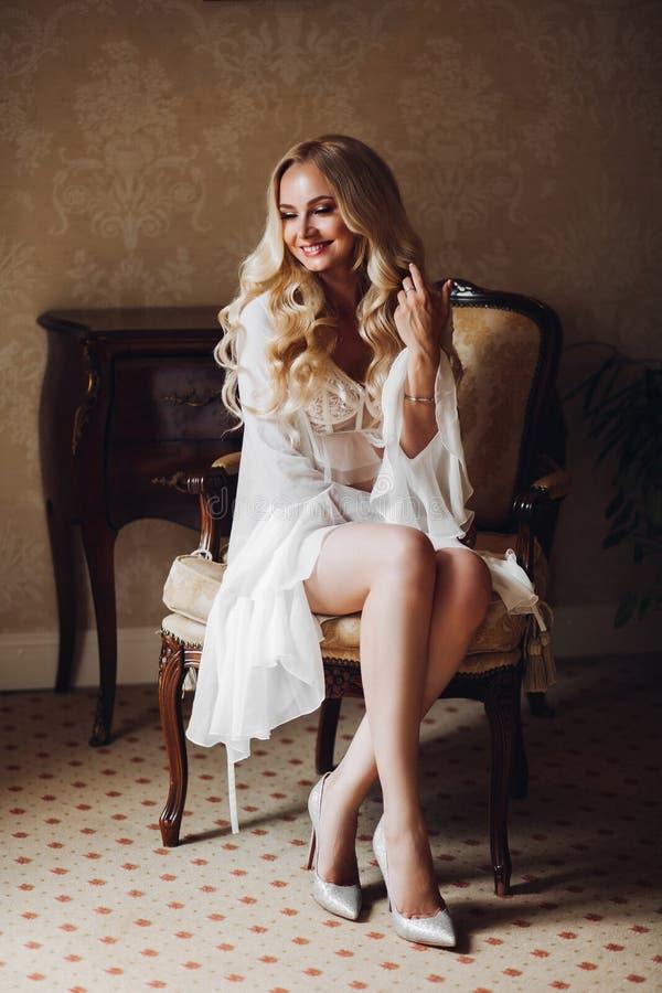 Συνεδρίαση νυφών αισθησιασμού blondie στην καρέκλα στο εσωτερικό πολυτέλειας στοκ φωτογραφία με δικαίωμα ελεύθερης χρήσης