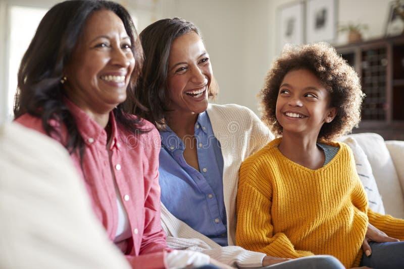 Συνεδρίαση ομάδας οικογενειακών θηλυκή οικογενειών τριών γενεάς σε έναν καναπέ στο καθιστικό που προσέχει τη TV και που γελά, εκλ στοκ εικόνα με δικαίωμα ελεύθερης χρήσης